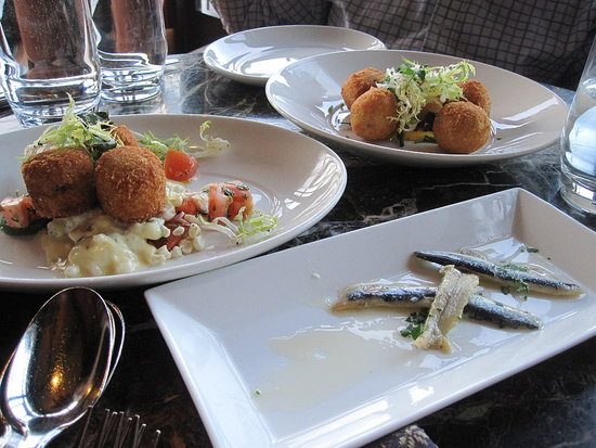 Behind the boquerones are crab cakes and arancini.