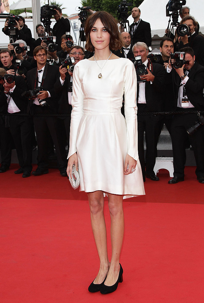 A demure Alexa in a high-necked white frock with simple, black low-heeled pumps.