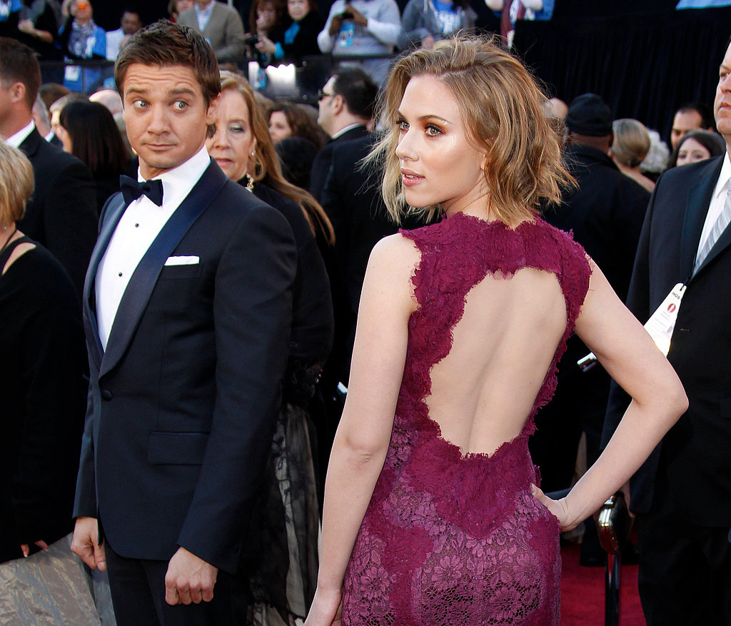 Scarlett posed on the red carpet at the 2011 Oscars while a dazed Jeremy Renner looked on.