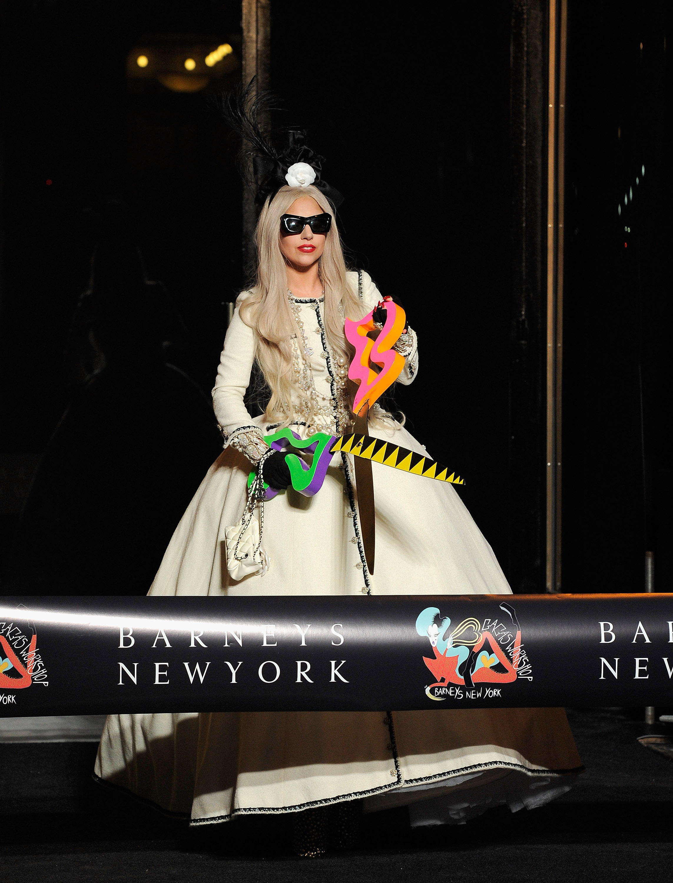 Lady Gaga used an oversized pair of scissors at Barneys New York.