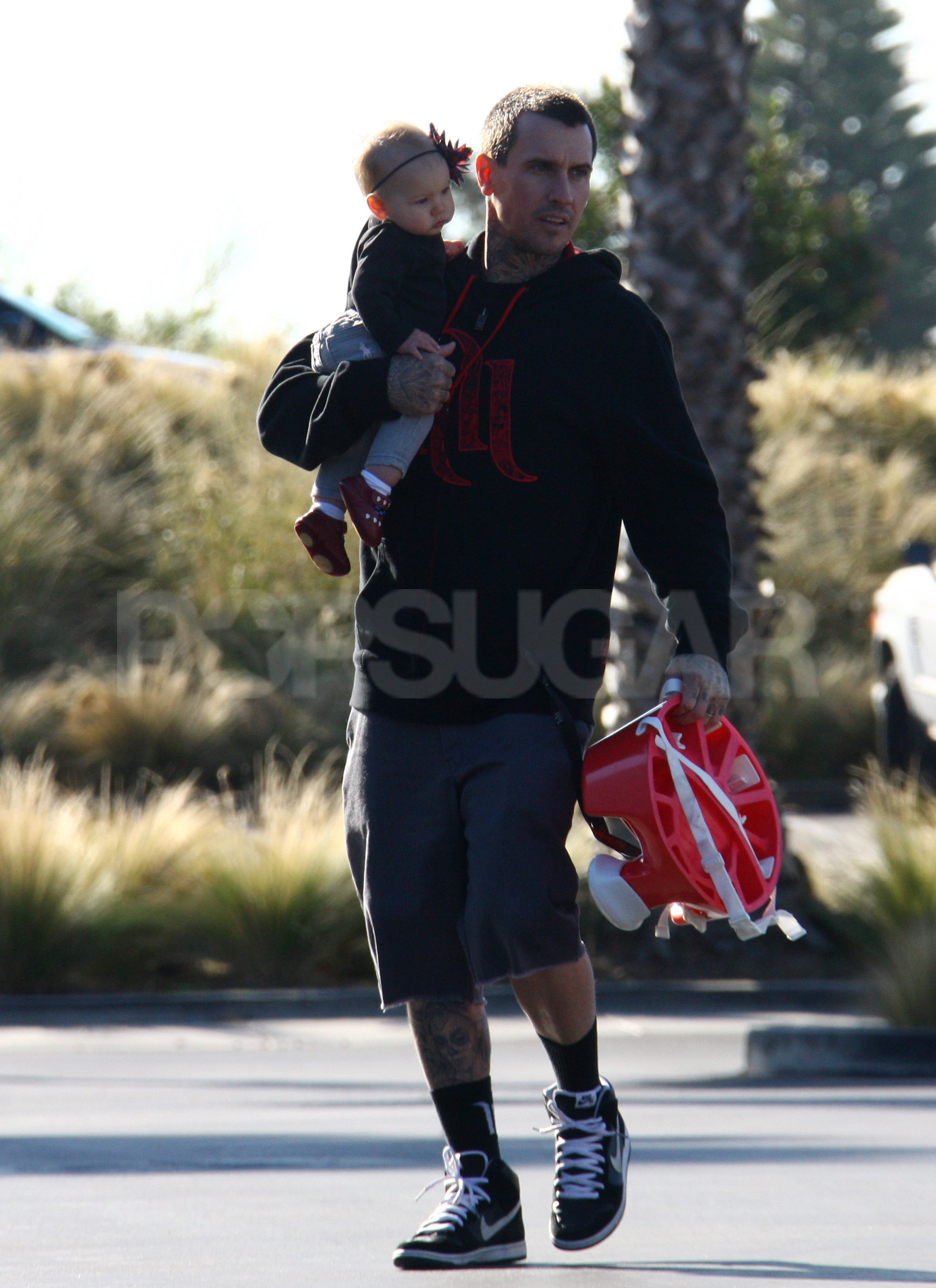 Carey Hart carried baby Willow in the crook of his arm.