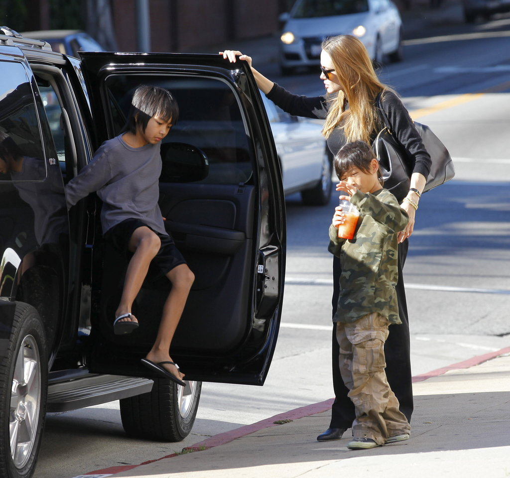 Pax Jolie-Pitt sipped some juice while Angelina Jolie helped Maddox out of a car.