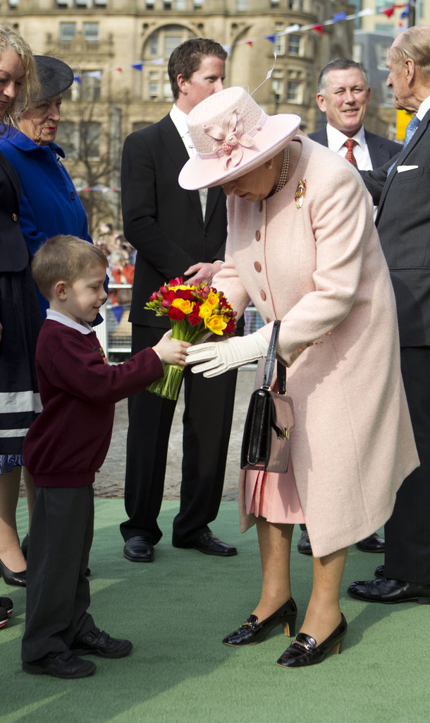 The queen accepted flowers from a young boy as she arrived at Manchester's town hall on March 23.