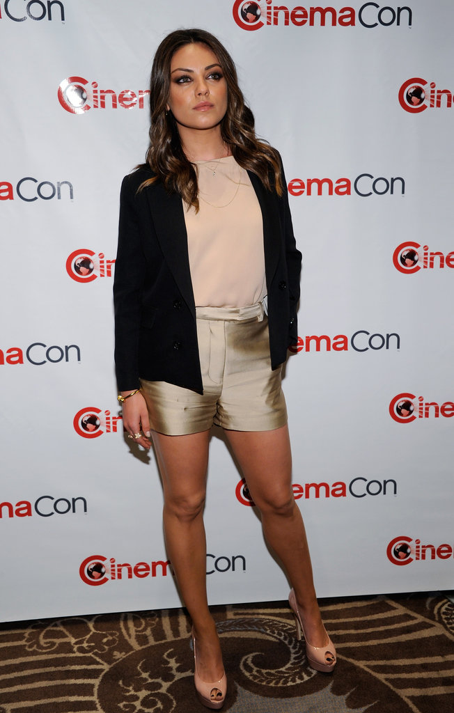 Mila Kunis donned a pair of gold shorts to the CinemaCon event in Las Vegas.