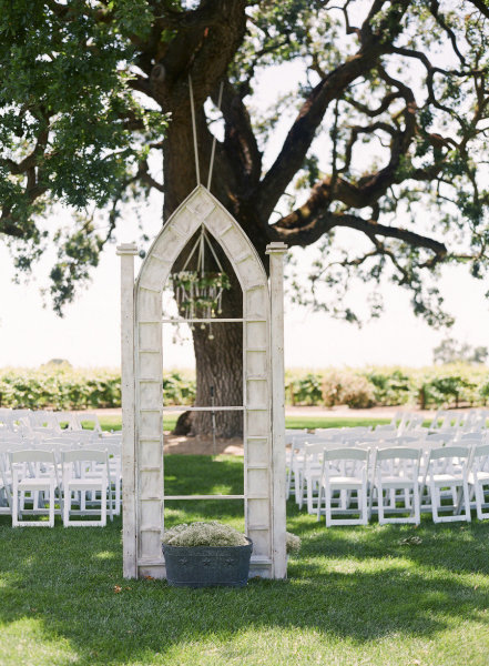 """Create your own """"outdoor chapel"""" with standing arches at the end of the aisle, and then add a crystal chandelier to amp up the romance. Photo by Tanja Lippert Photography via Style Me Pretty"""