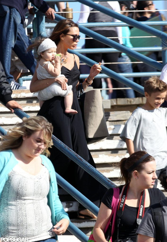 Victoria Beckham carried daughter Harper Beckham at the Santa Monica Pier with son Romeo Beckham.