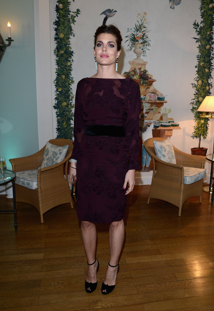 We love Charlotte's decadent, moody sheath dress and statement earrings at a Gucci party in Cannes.