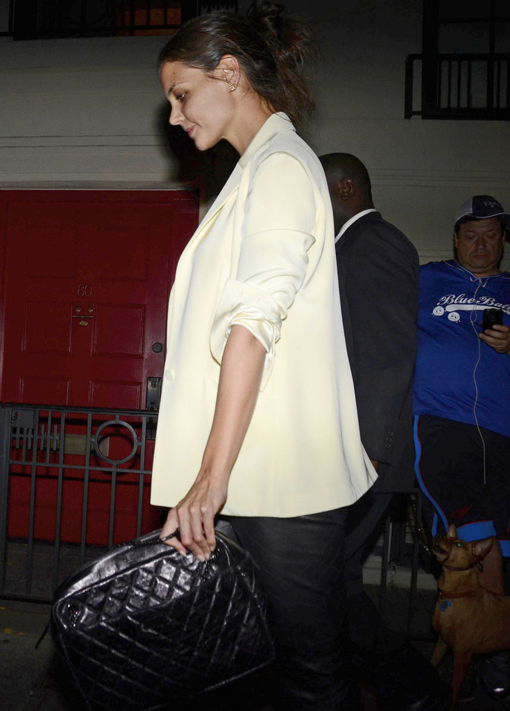 Katie Holmes paired a white blazer with a black clutch.