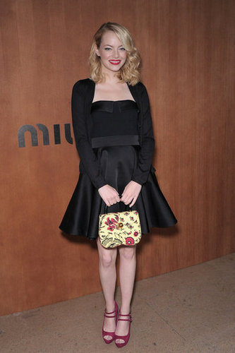 Emma Stone stuck to her signature fit-and-flare silhouette, but in a chic black set, at Miu Miu. Her bold red lip, printed purse, and magenta  double-strap pumps finished off the look.