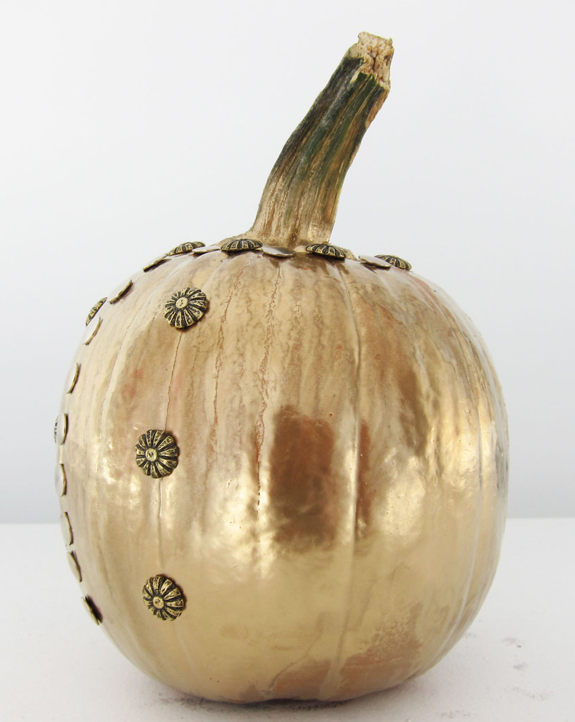 Start inserting your studs/embellishments of choice once the metallic spray paint finish is completely dry. Quick tip: use the natural pumpkin striations as an easy guide.