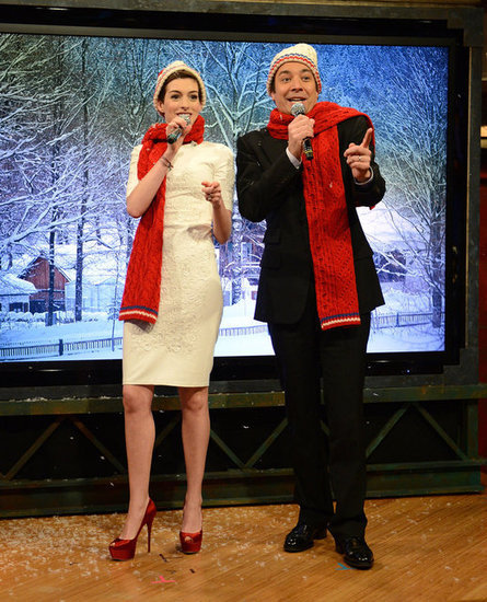 Anne Hathaway stopped by Jimmy Fallon's Late Night show to play a game of Mad Lib Christmas carols, replacing key verbs, nouns, and adjectives with words randomly picked by the studio audience.