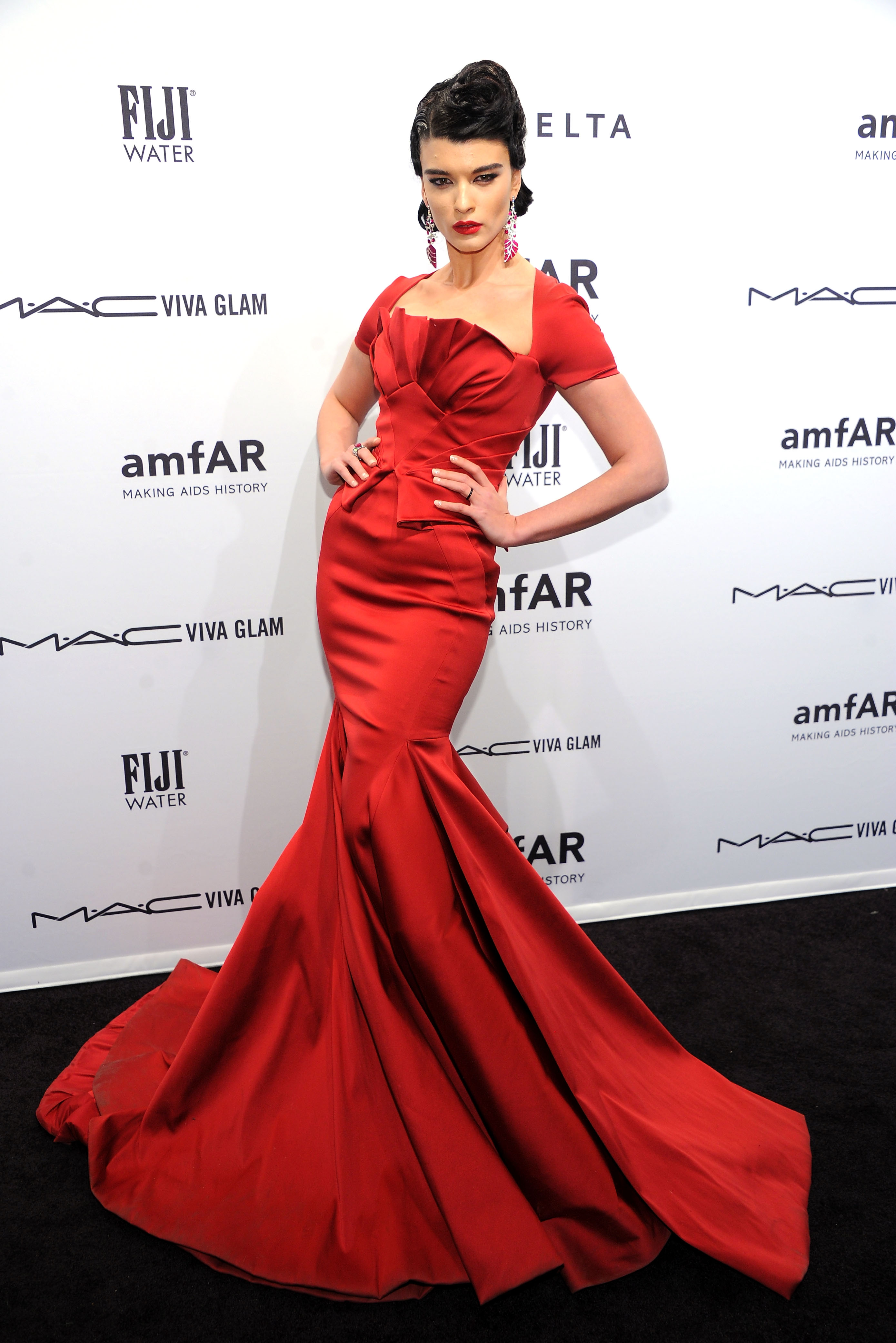 Crystal Renn attended the amfAR New York Gala in a floor-length red gown by Zac Posen.