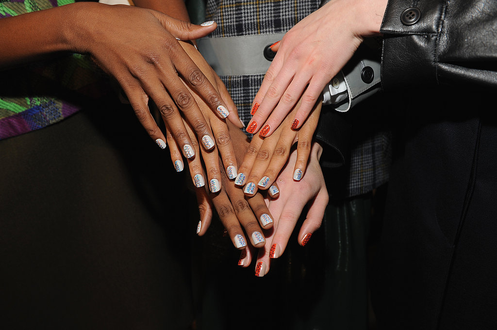 The nails, by CND, were inspired by urban art in the '80s . . . and by the clothes themselves. Split down the center and patterned on one side, the colors were chosen based on the models' skin tone.