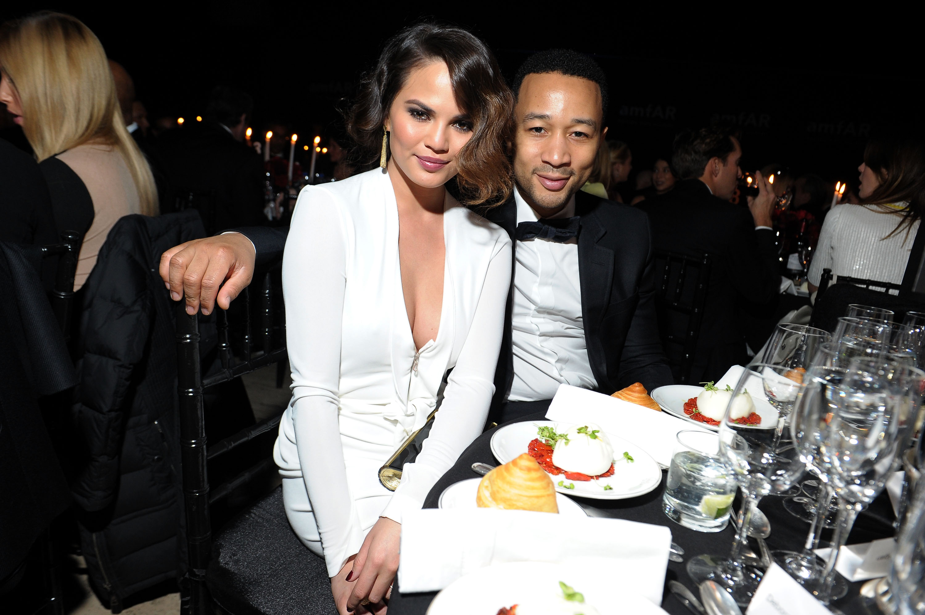 John Legend and Chrissy Teigen cuddled up during the amfAR New York Gala on Wednesday.
