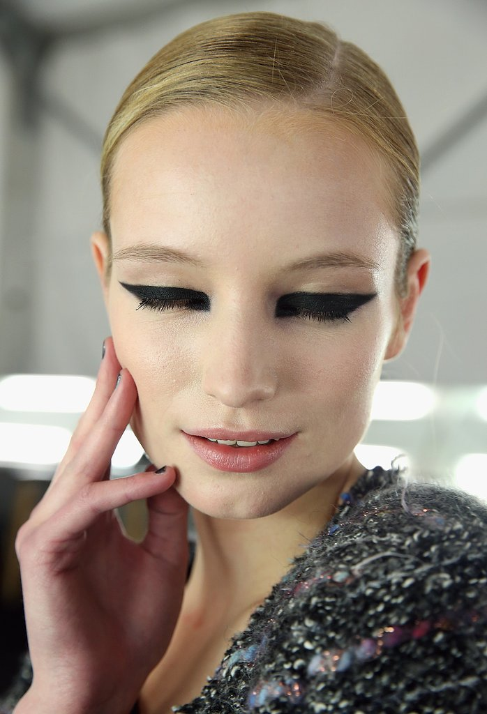 """The detail is a strong, graphic eyeliner that's quite rectangular and elongated,"" lead makeup artist Val Garland explained. ""Since it's such a strong look on the eye, to keep it looking modern, we thought [it was necessary to do] beautiful skin and a natural lip. That keeps it looking street and edgy."" To create the look, she used MAC Blacktrack to make a square shape at the inner corners and continued the line to the outer corners and underneath the eye. She topped the liner with eye shadow in Carbon to give it a fuzzy appearance."