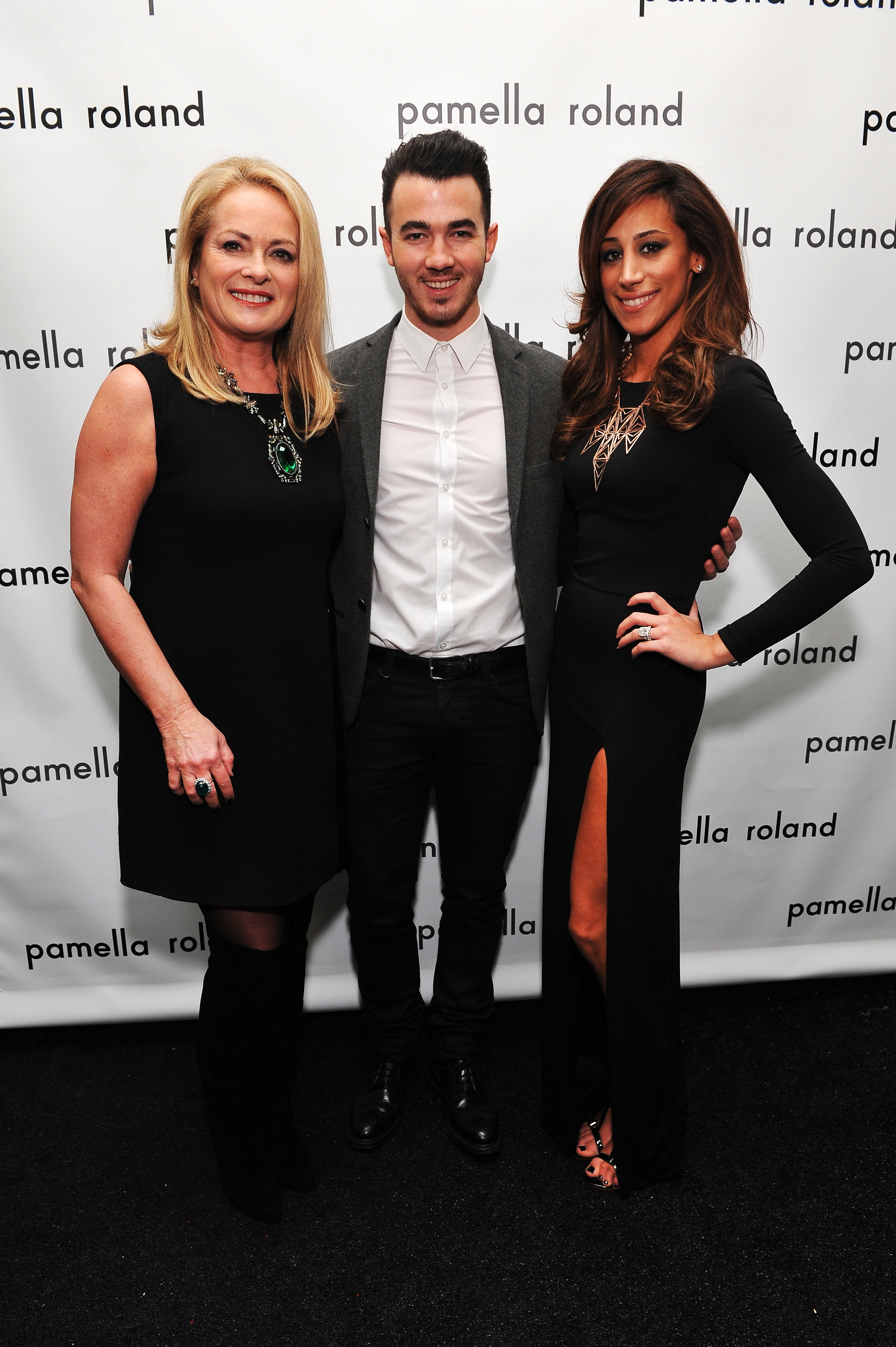 Kevin and Danielle Jonas stopped to pose with designer Pamella Rowland before her Monday show.