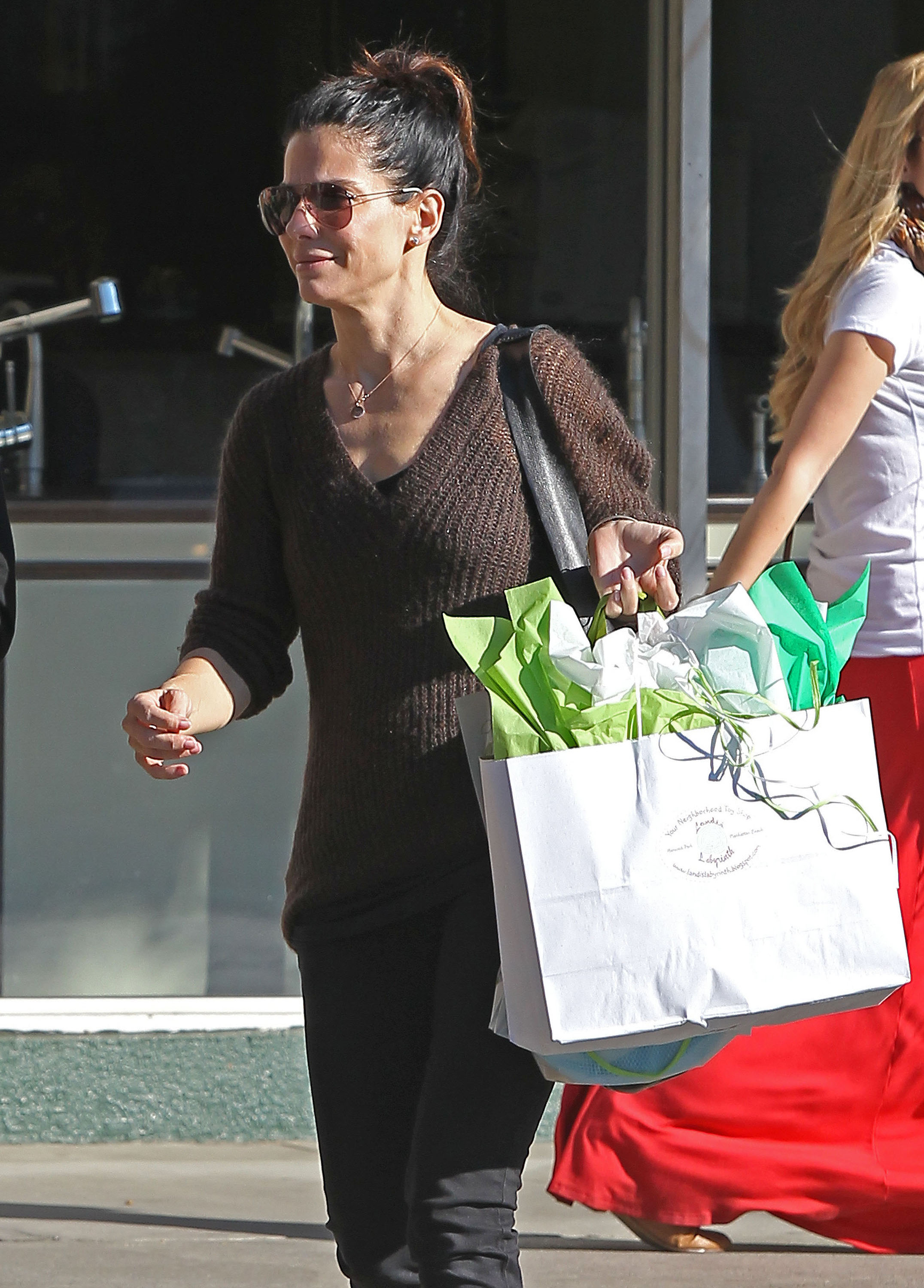 Sandra Bullock carried a gift out of a toy store.