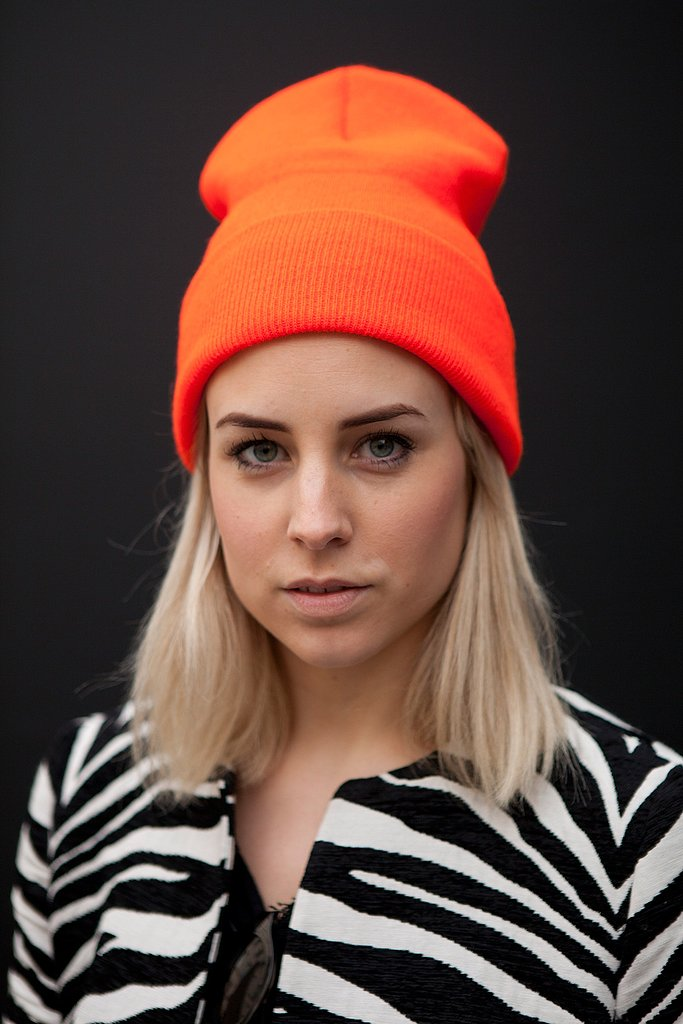 A bright orange beanie came to life against a zebra-print coat.