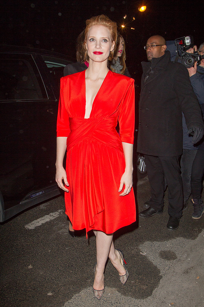 Jessica Chastain popped against the Parisian background in a red plunging dress and pointy Christian Louboutin pumps while arriving to the Saint Laurent show.