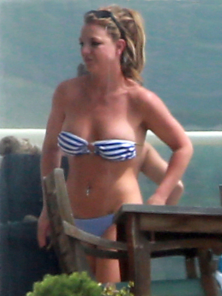 Britney Spears donned a striped bikini to soak in the sun with friends in Malibu, CA.