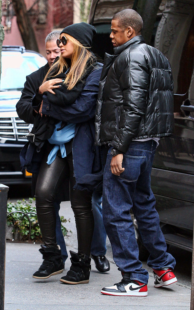 Beyoncé carried baby Blue Ivy in slick leather pants and a black beanie, while Jay-Z followed behind in a stylish puffer jacket and Nikes in February 2012.