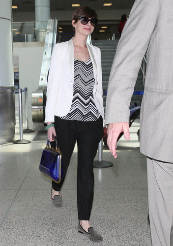 Anne Hathaway traveled chicly in a black and white chevron-print Ella Moss tank, a white tuxedo blazer, and black trousers. She completed her two-tone ensemble with a studded loafers, a blue structured bag, and cat-eye sunglasses.