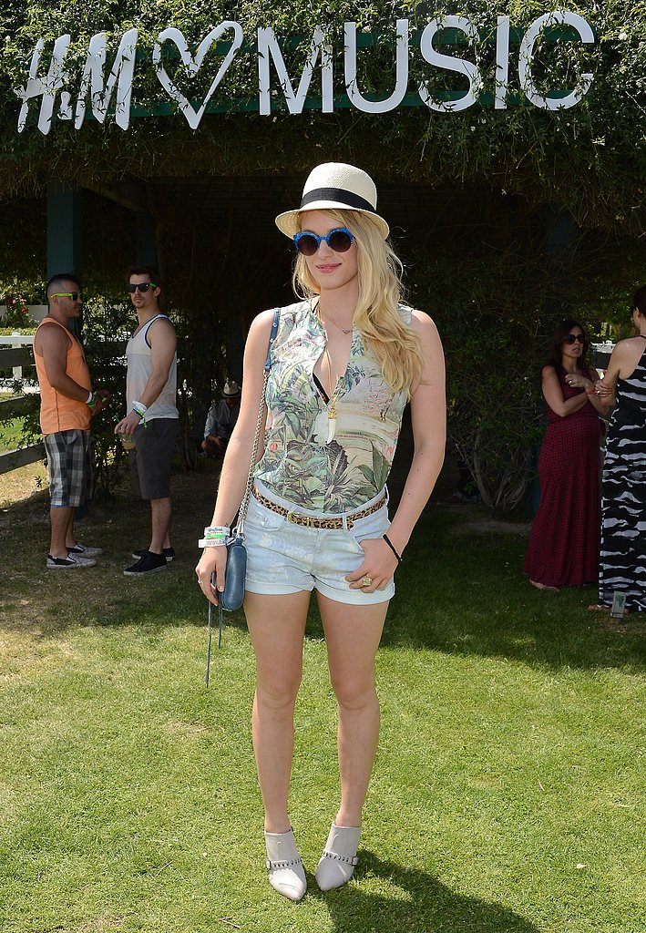 At H&M's daytime affair, Leven Rambin tucked a printed sleeveless blouse into denim shorts, then added loads of fun accessories: a leopard belt, fedora, blue-rimmed sunglasses, and gray studded booties.