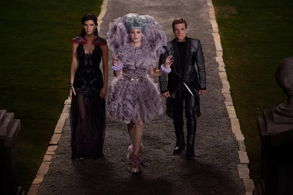 Jennifer Lawrence as Katniss, Elizabeth Banks as Effie, and Josh Hutcherson as Peeta in Catching Fire.
