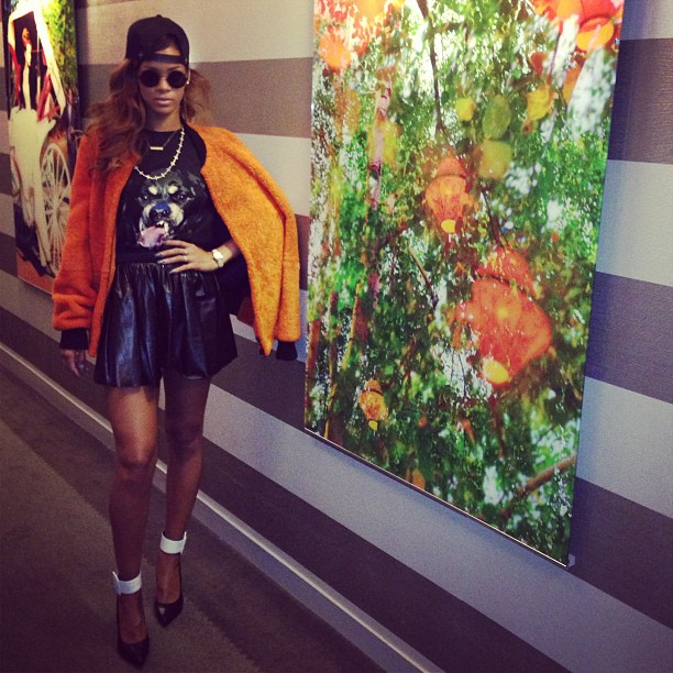 Rihanna sported a leather skirt and backward baseball cap while posing next to a piece of art. Source: Instagram user badgalriri