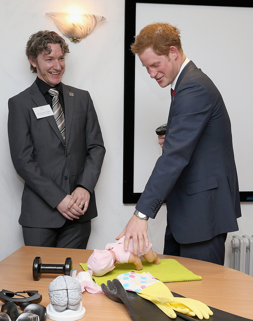 Prince Harry attempted to change a baby's diaper while holding a weight in one hand.