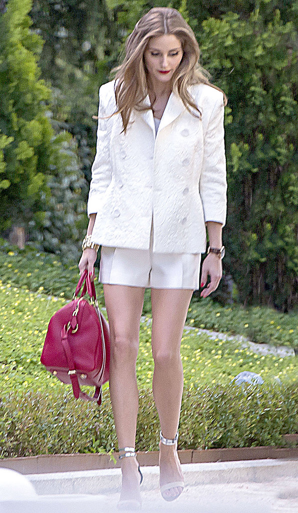 Olivia donned another sharp shorts suit in Madrid, then accessorized via a red satchel and silver ankle-strap sandals.