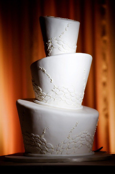 We love how uniquely shaped tiers modernize this all-white cake. Photo by cakelava via Style Me Pretty