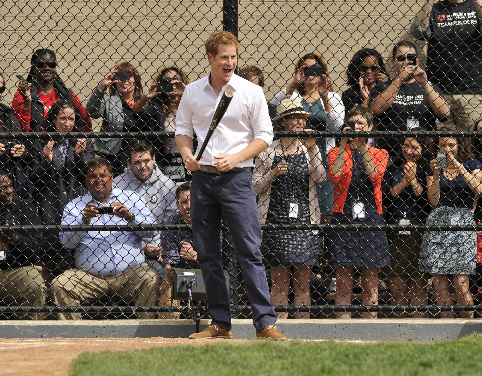 A group of fans watched Prince Harry while he tried his hand at baseball in NYC's Harlem neighborhood in May 2013.