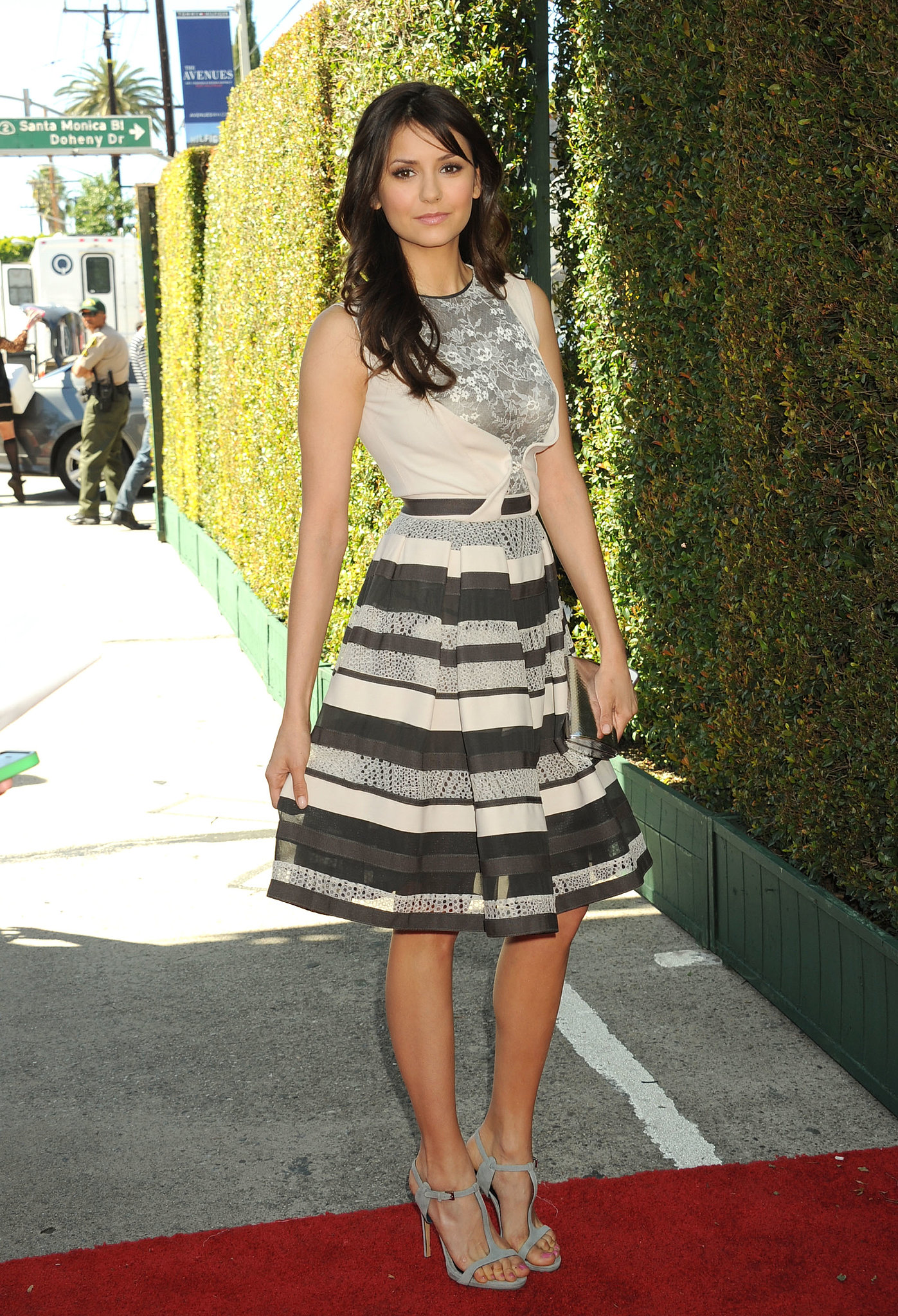 For the 10th Annual John Varvatos Stuart House Benefit, Nina Dobrev wore a lace-and-striped Elie Saab fit-and-flare with gray suede t-strap sandals and a silver metallic clutch.