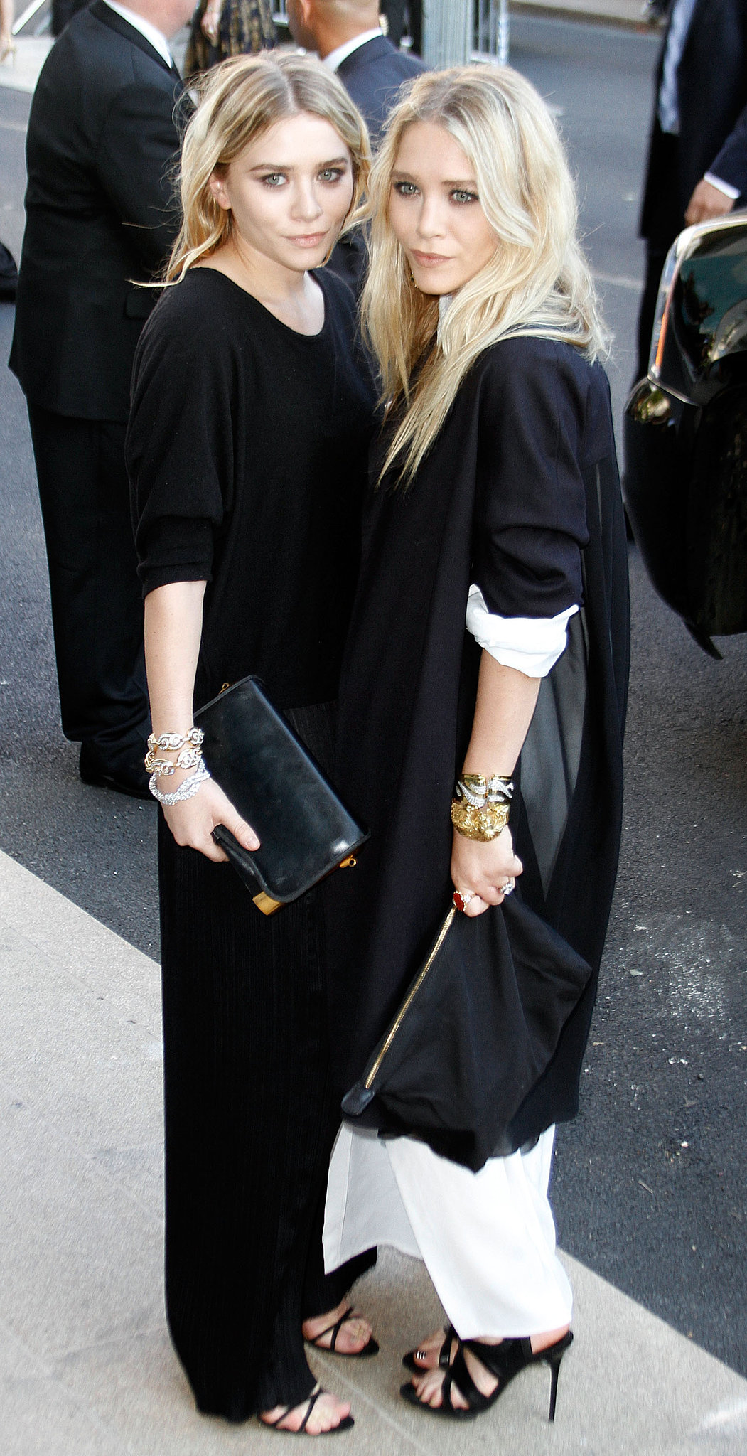 Twinning combo: Stacks of bracelets, slick black clutches, and strappy sandals? Check! The girls were ready to take on the big city in June 2007.  Ashley added a dash of dazzle to her black-on-black look with three diamond bracelets. Mary-Kate layered an oversize black jacket over her white maxi, then slipped on a few animal bangles for the final touch.