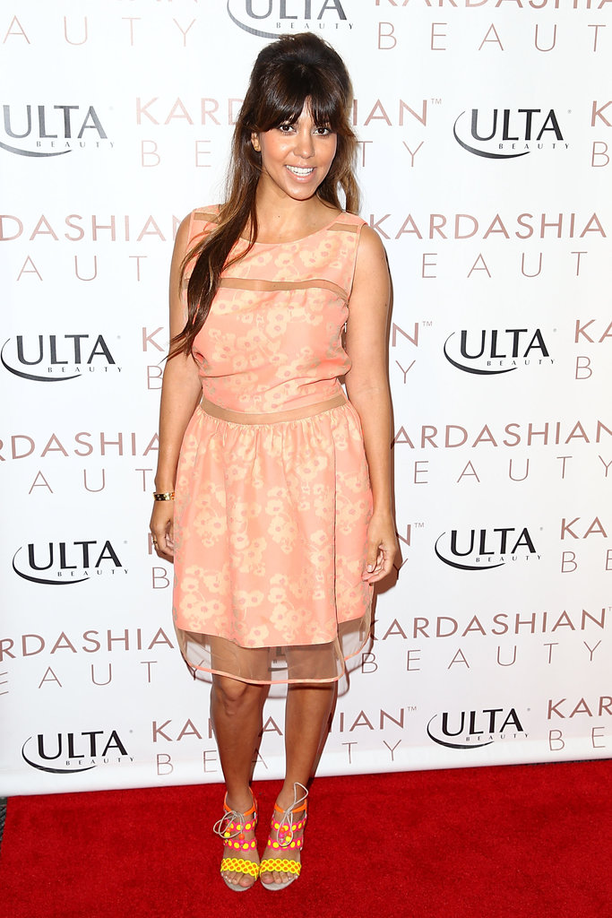 At a Kardashian Beauty event in Huntington Beach, Kourtney Kardashian's multicolored lace-up sandals helped punch up her peachy dress.