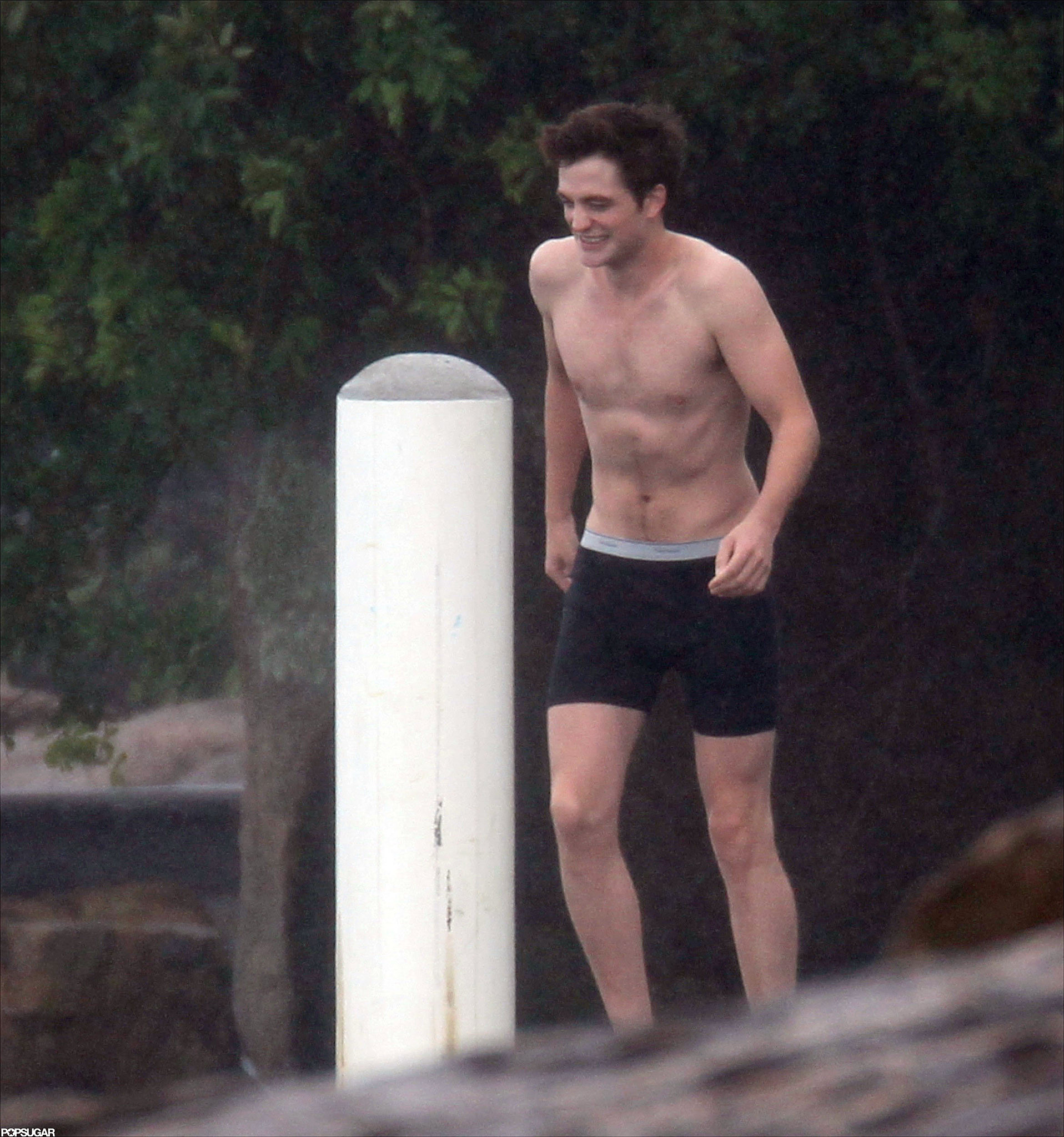 Robert Pattinson took off his shirt to jump in the water in Rio de Janeiro in December 2010.