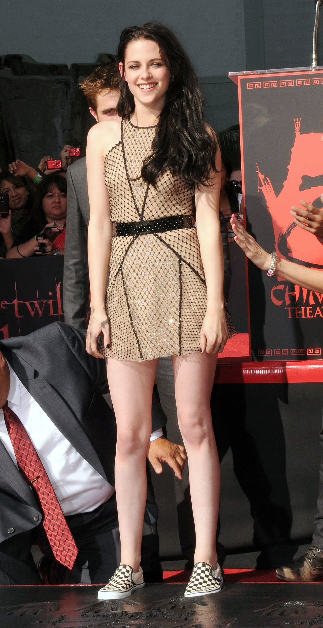 In November 2011, Stewart arrived at the Hollywood handprint ceremony in a sheer, shortened Marios Schwab dress and suede Brian Atwood platforms, which she quickly swapped for checkered Vans slip-ons.