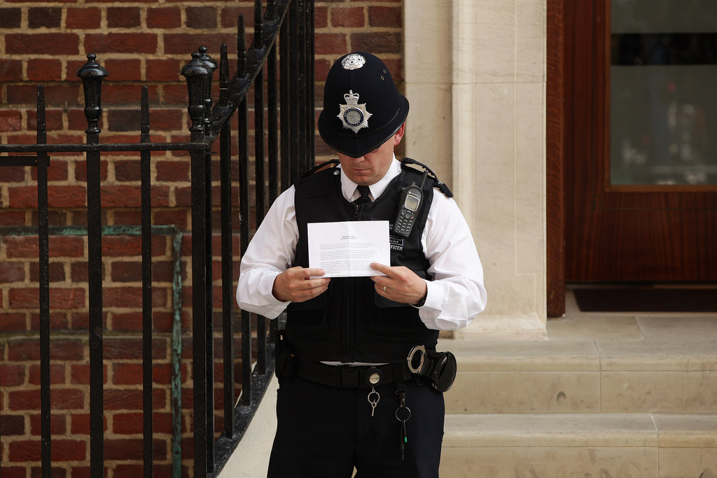A police officer read his notes outside the Lindo Wing.