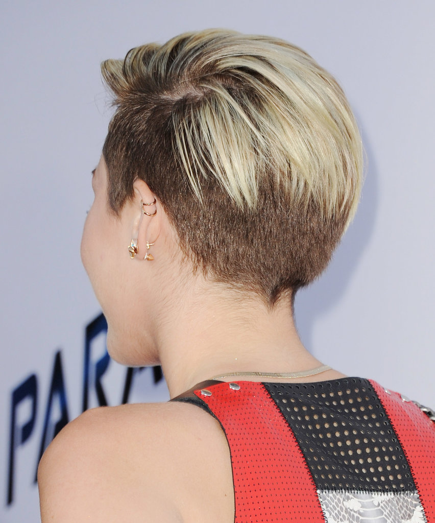 Miley's deep part also covered some of her shaved hair in the back.