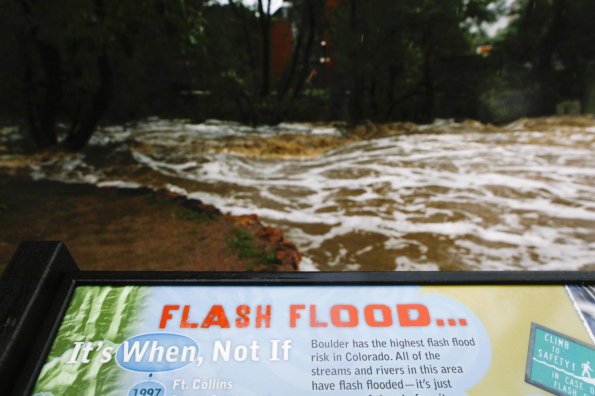 A flash flood sign stood near Boulder Creek, which overflowed following heavy rains.