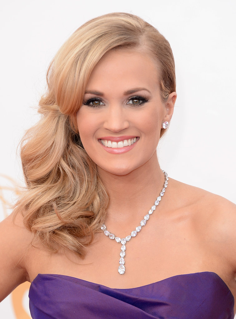 Carrie Underwood has a formula for red carpet success: sideswept waves, smoky eyes, and soft pink lipstick.