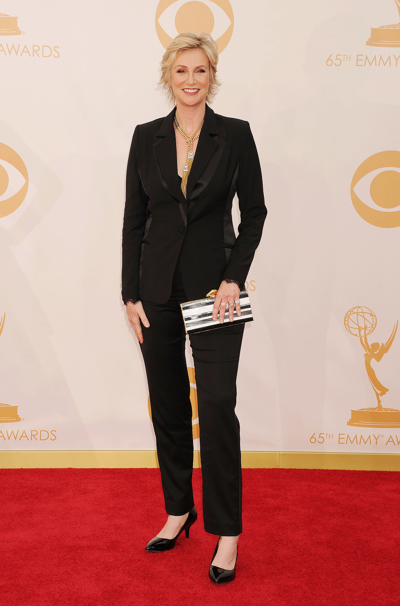 Jane Lynch completed a sharp suit with a pair of black kitten heels, bold gold jewels, and a striped clutch.