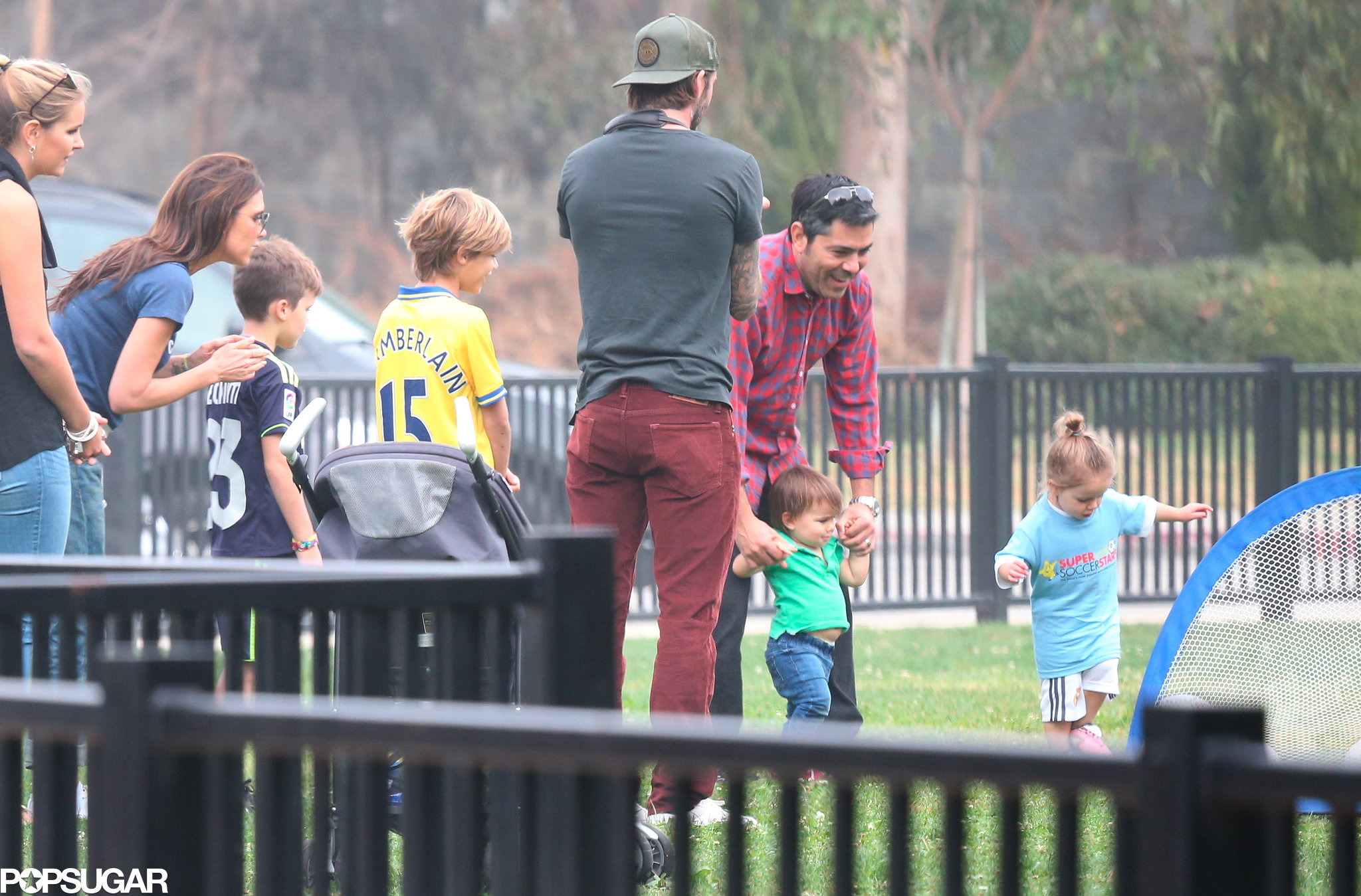 The Beckhams stood together to watch little Harper play soccer.