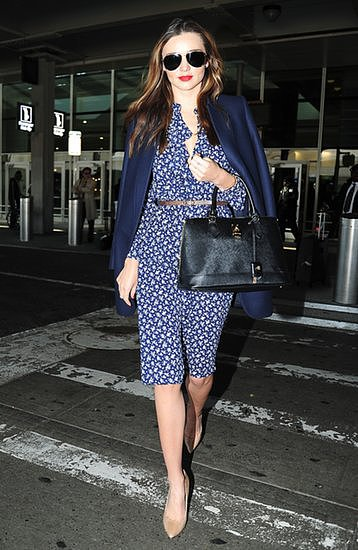A printed dress, pumps and navy blazer bring polish to Miranda Kerr's airport look.