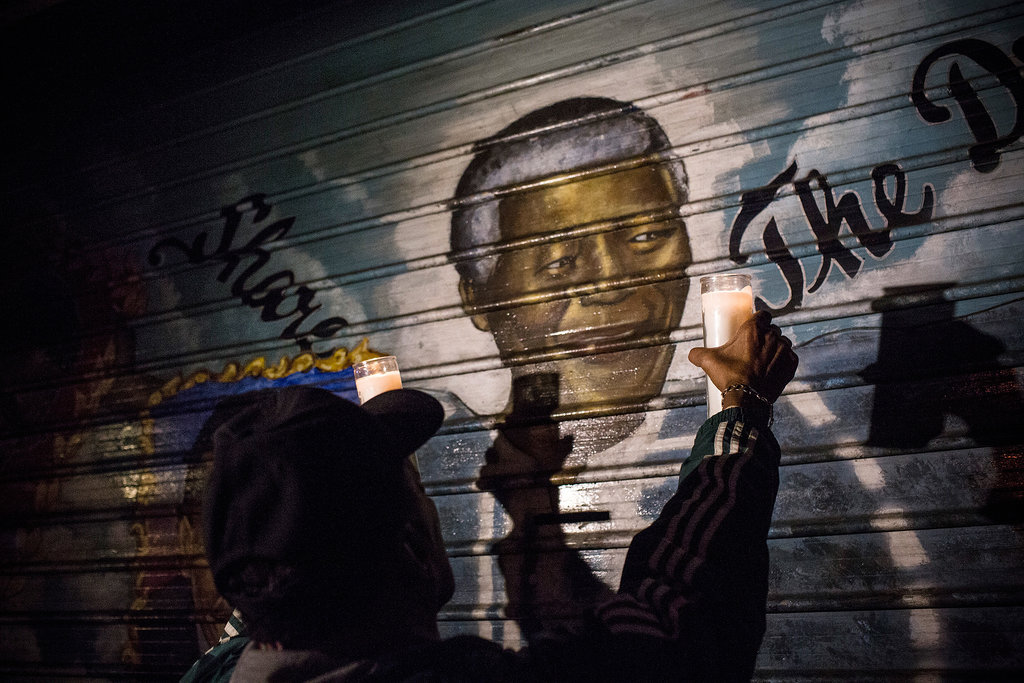 A man held up candles to a Nelson Mandela mural in NYC.
