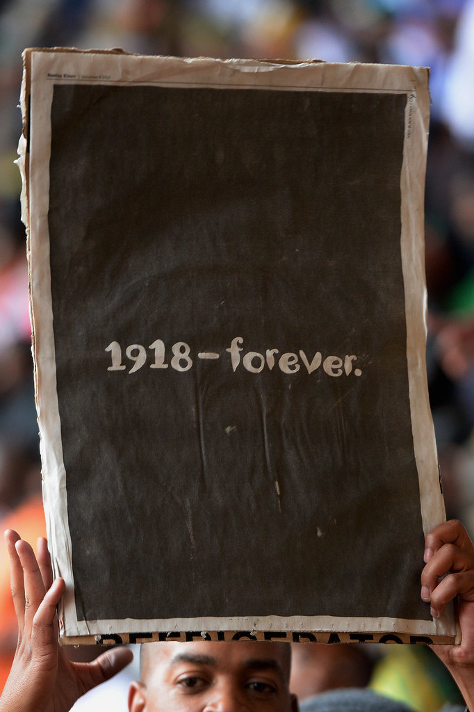 A man held up a page from the local newspaper during Nelson Mandela's official memorial in South Africa.