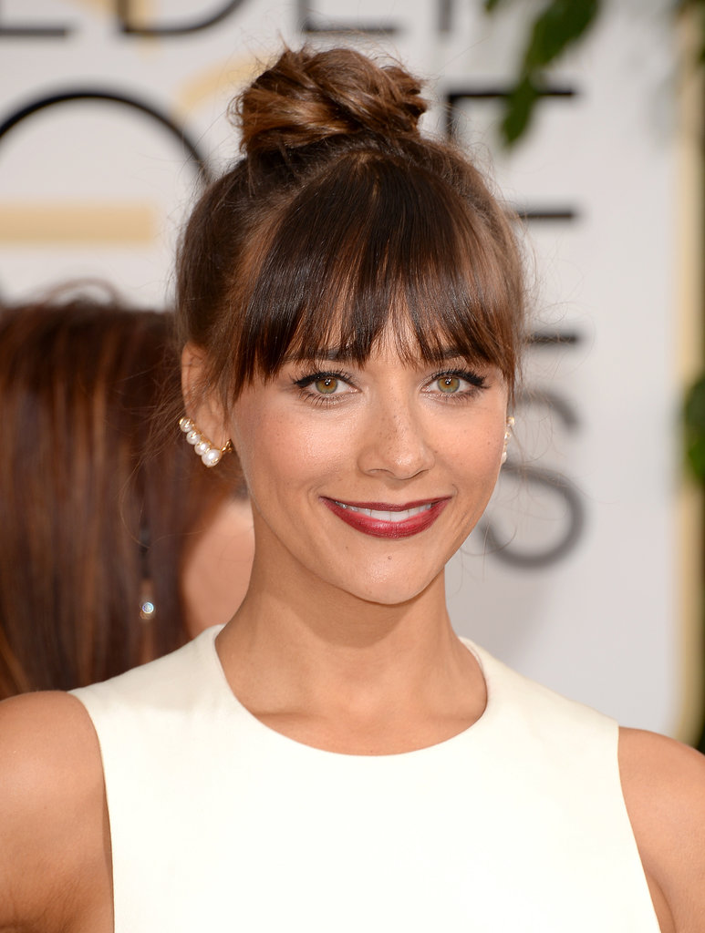 Rashida Jones topped the beauty trends with a braided bun, piecey bangs, and a very berry lip.