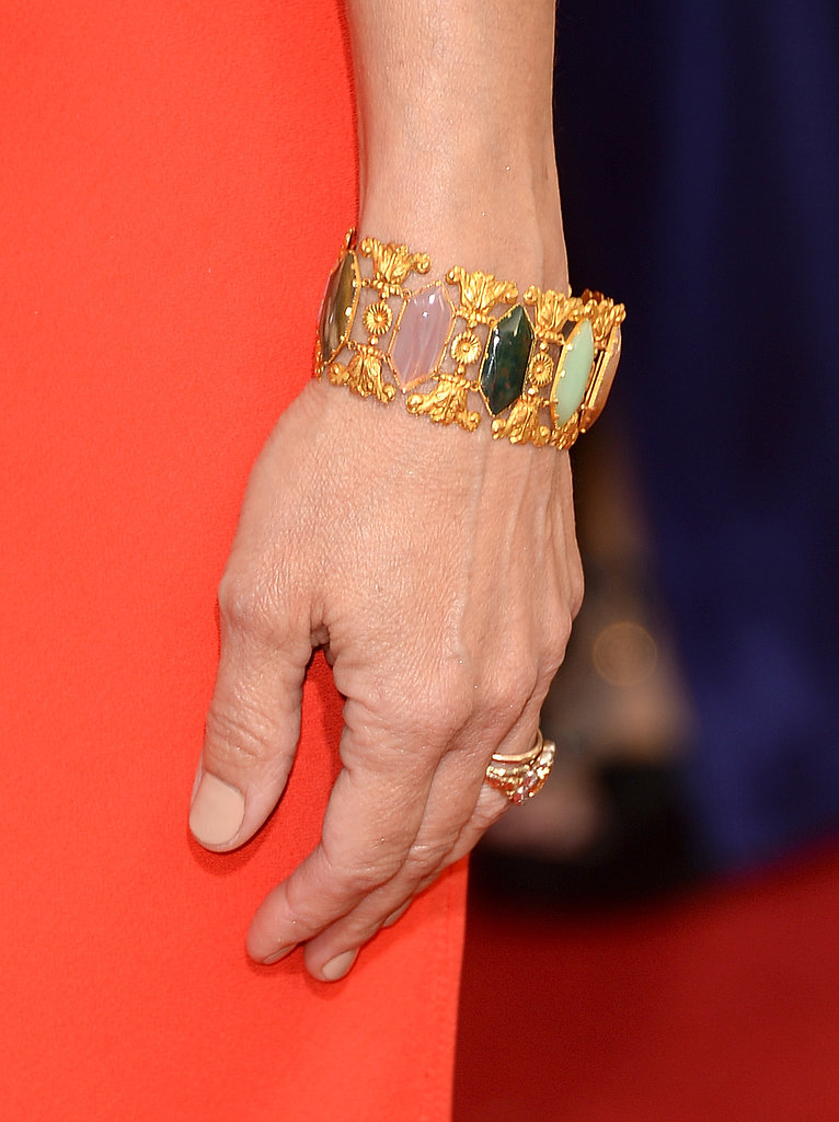 Julia Louis-Dreyfus added a multicolored jeweled cuff to her bright red Narciso Rodriguez gown.