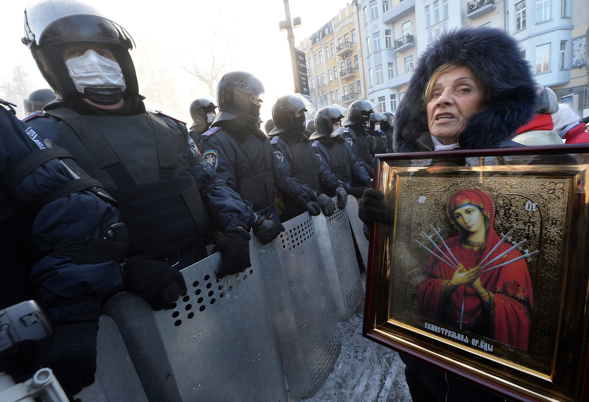 One woman held up a religious image while standing in front of riot police in Kiev.